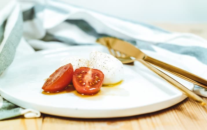 Are Tomatoes Keto? sliced tomato and mozzarella cheese on white plate beside brass-colored knife and fork